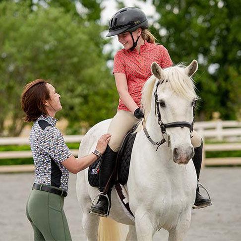 Woman talking to child on horseback
