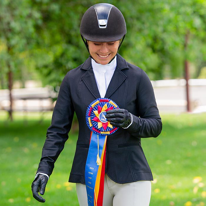 Woman in horse show outfit smiling and holding a long champion ribbon