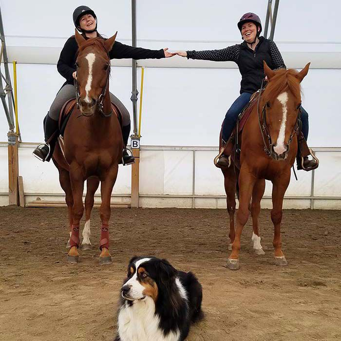 Two women on two separate horses holding hands, with a dog in the middle